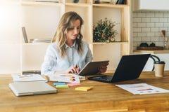 La mujer joven de la empresaria se está sentando en la tabla de cocina y utiliza la tableta, funcionamiento, estudiando Fotografía de archivo libre de regalías