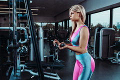 La mujer joven de la aptitud ejecuta ejercicio con la cruce del cable de la ejercicio-máquina en gimnasio fotos de archivo libres de regalías
