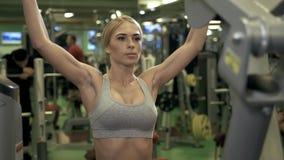 La mujer joven de la aptitud ejecuta ejercicio con la ejercicio-máquina en gimnasio almacen de video