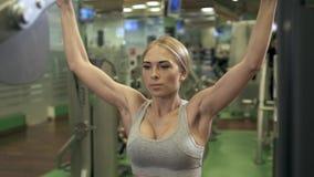 La mujer joven de la aptitud ejecuta ejercicio con la ejercicio-máquina en gimnasio almacen de metraje de vídeo