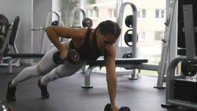 La mujer joven de la aptitud que hace pesa de gimnasia rema en el gimnasio del crossfit Muchacha juguetona que ejercita - peso de metrajes