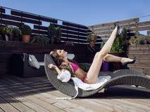 La mujer joven de la belleza después del balneario en bikini y el traje en el hotel recurren, en terraza gozando del sol caliente Foto de archivo