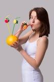 La mujer joven de la belleza guarda la naranja y bebe el jugo con la paja Foto de archivo
