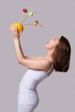 La mujer joven de la belleza guarda la naranja y bebe el jugo a partir de una paja Imagen de archivo libre de regalías