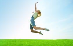La mujer joven de la belleza salta en campo Imagenes de archivo