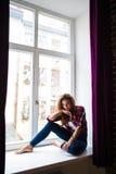 La mujer joven de la belleza se relaja en fondo del alféizar Foto de archivo libre de regalías