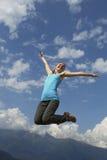 La mujer joven de la felicidad está saltando contra el cielo azul Día asoleado del verano Fotos de archivo