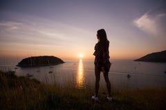 La mujer joven de la libertad disfruta de puesta del sol del océano en pico de montaña Foto de archivo
