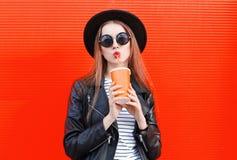 La mujer joven de la moda bebe el zumo de fruta fresca de la taza en el estilo negro de la roca que se divierte sobre rojo colori Fotos de archivo