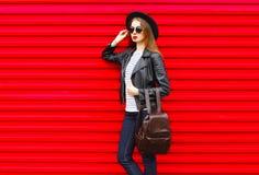 La mujer joven de la moda en estilo negro de la roca se coloca sobre rojo vacío Imágenes de archivo libres de regalías