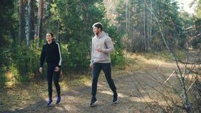 La mujer joven de los pares felices y su marido están haciendo deportes en el parque que salta en la tierra y la sonrisa Forma de almacen de video