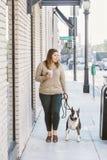 La mujer joven de Milllennial camina su perro mientras que sorbe el café imagenes de archivo