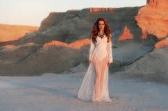 La mujer joven de moda en un vestido largo blanco se está colocando en la arena en un fondo del barranco en la puesta del sol Est foto de archivo