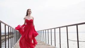 La mujer joven de la moda en vestido largo está huyendo sobre el muelle de transbordador viejo, vista delantera metrajes