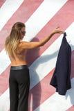 La mujer joven de moda hermosa se está colocando cerca de la pared rayada con el trasero desnudo y está sosteniendo chaqueta Fotos de archivo