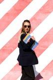 La mujer joven de moda hermosa se está colocando cerca de la pared rayada y está sosteniendo una carpeta Imagen de archivo libre de regalías