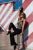 La mujer joven de moda hermosa se está sentando en una silla cerca de la pared rayada Fotos de archivo libres de regalías