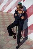La mujer joven de moda hermosa se está sentando en una silla cerca de la pared rayada Foto de archivo
