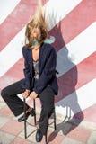 La mujer joven de moda hermosa se está sentando en una silla cerca de la pared rayada y sacude su pelo Fotos de archivo
