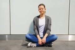 La mujer joven de moda hermosa se sienta en la calle por la pared con Fotografía de archivo