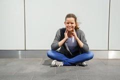 La mujer joven de moda hermosa se sienta en la calle por la pared con Imagen de archivo libre de regalías