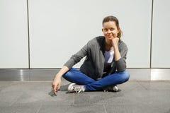 La mujer joven de moda hermosa se sienta en la calle por la pared con Fotografía de archivo libre de regalías