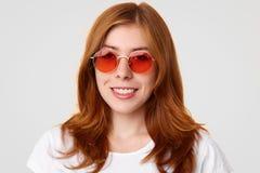 La mujer joven de moda preciosa positiva con sonrisa apacible, lleva las gafas de sol de moda rojas, estando en buen humor, disfr Fotos de archivo
