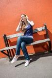 La mujer joven de moda que disfruta del cierre observa en escuchar la música Foto de archivo