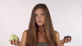 La mujer joven de pelo largo que elegía entre una manzana y un buñuelo aisló imagenes de archivo