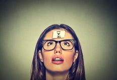 La mujer joven de pensamiento con la arena registra la etiqueta engomada de la muestra en su frente Foto de archivo