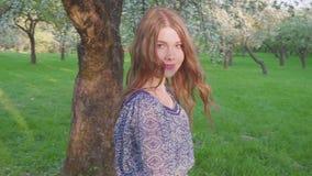 La mujer joven de tentación que camina en un manzanar en la primavera florece blanco r almacen de metraje de vídeo