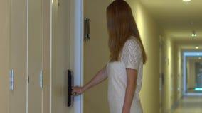 La mujer joven deja su apartamento y cierra una cerradura electrónica almacen de metraje de vídeo