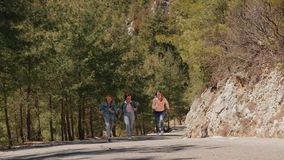 La mujer joven del árbol en vaqueros lleva divertirse en el camino forestal almacen de video