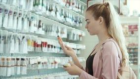 La mujer joven del artista está examinando los tubos con los tintes en una tienda profesional almacen de metraje de vídeo
