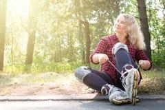 La mujer joven del blonge ata cordones en sus botas del rodillo imagenes de archivo