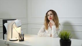 La mujer joven del empleado de oficina está procrastinando la sentada en el trabajo en la tabla de la oficina almacen de metraje de vídeo