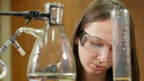 La mujer joven del estudiante que trabaja con las sustancias químicas y escribe los resultados en universidad Gafas de seguridad  almacen de metraje de vídeo