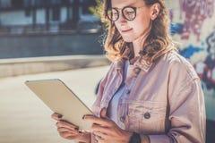 La mujer joven del inconformista en vidrios se coloca en la calle de la ciudad y utiliza la tableta Muchacha que mira en la panta fotos de archivo