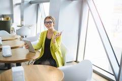 La mujer joven del negocio en vidrios trabaja en una tabla en un caf? imagenes de archivo