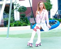 La mujer joven del pelirrojo está balanceando en un oscilación en verano Un equipo de la tendencia de la moda Chaqueta rosada y v Foto de archivo libre de regalías