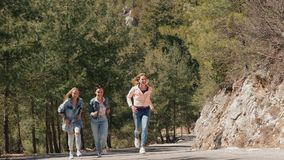 La mujer joven del ?rbol en vaqueros lleva divertirse en el camino forestal almacen de metraje de vídeo