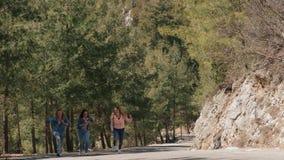 La mujer joven del ?rbol en vaqueros lleva divertirse en el camino forestal almacen de video