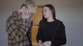 La mujer joven del retrato que muestra dos fingeres que llevan a cabo la prueba de embarazo el hombre es trastornada y confundida almacen de video