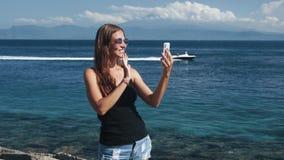 La mujer joven del viajero tiene charla video el vacaciones de verano La muchacha hace el vídeo del selfie almacen de metraje de vídeo