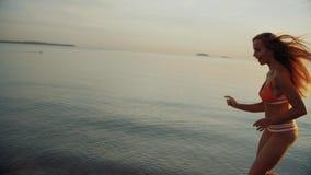 La mujer joven delgada corre por la tarde en la puesta del sol almacen de video