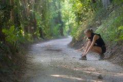La mujer joven deportiva ata el zapato fotos de archivo