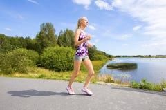 La mujer joven deportiva corre en el camino a lo largo del agua Fotografía de archivo libre de regalías