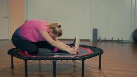La mujer joven deportiva está haciendo estirando ejercicios en el entrenamiento de la aptitud en el gimnasio almacen de metraje de vídeo