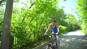 La mujer joven deportiva hermosa monta su bici de la manera feliz y positiva en verano caliente Vidrios que llevan de la muchacha metrajes