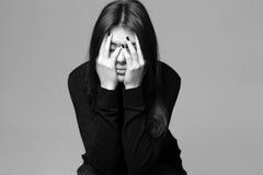 La mujer joven deprimida con entrega su cabeza Foto de archivo libre de regalías